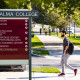 Male student walks by campus directory sign outside of Reid Knox admissions building.