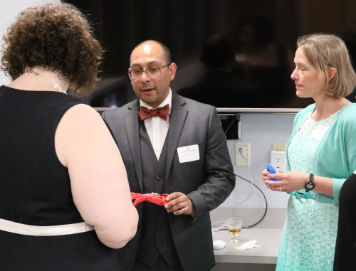 Victor Argueta-Diaz shows the basic prosthetic hand to guests at the St. Andrews Dinner.