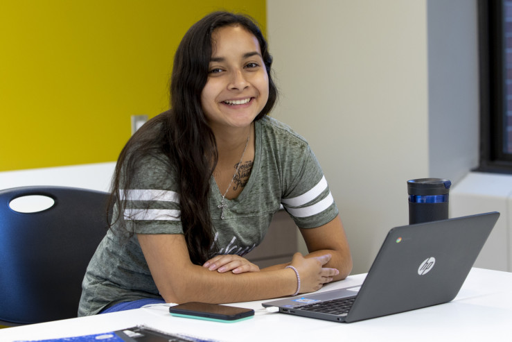 Student at desk smiling