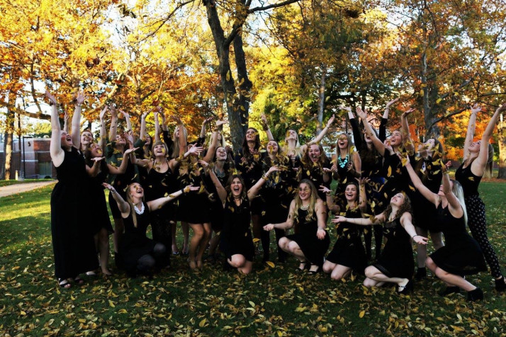 Sister of Alpha Xi Delta throwing leaves into the air