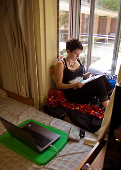 A student relaxes and studies in a sunny window in Bonbright Hall.