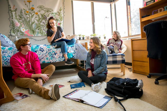 A group of students lounge in a remodeled Bruske Hall dorm room.
