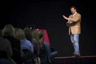 Neil DeGrasse Tyson presenting in Art Smith Arena on Alma College's campus.