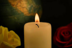 Photo shows a white pillar candle burning with white and red roses on at the foot and a globe in ...