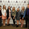 The seven ACE Scholar winners pose in front of an Alma College backdrop.