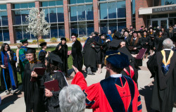 Alma College faculty form a gauntlet to honor the 2017 graduates.