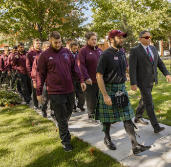 Chaplain Andrew Pomerville and Coach Jason Couch lead the football team in a pre-game march to Bahlke Field.