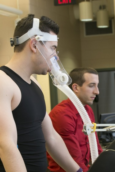 <em>Alex Montoye (right) studies the performance of the Hexoskin, a biometric smart shirt with sensors that measures heart rate, breathing volume, calories burned, steps taken and sleep.</em>