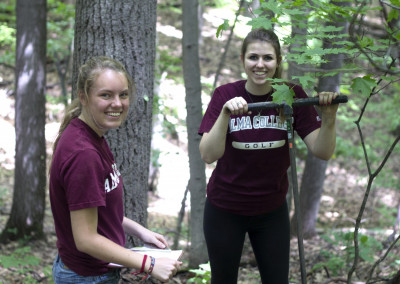 <em>Students plant trees at the Alma College Ecological Station.</em>