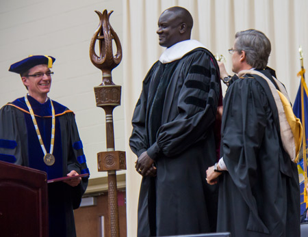 President Abernathy, left, and Board of Trustees Chair Stephen Meyer, right, present an honorary degree to John Dau.