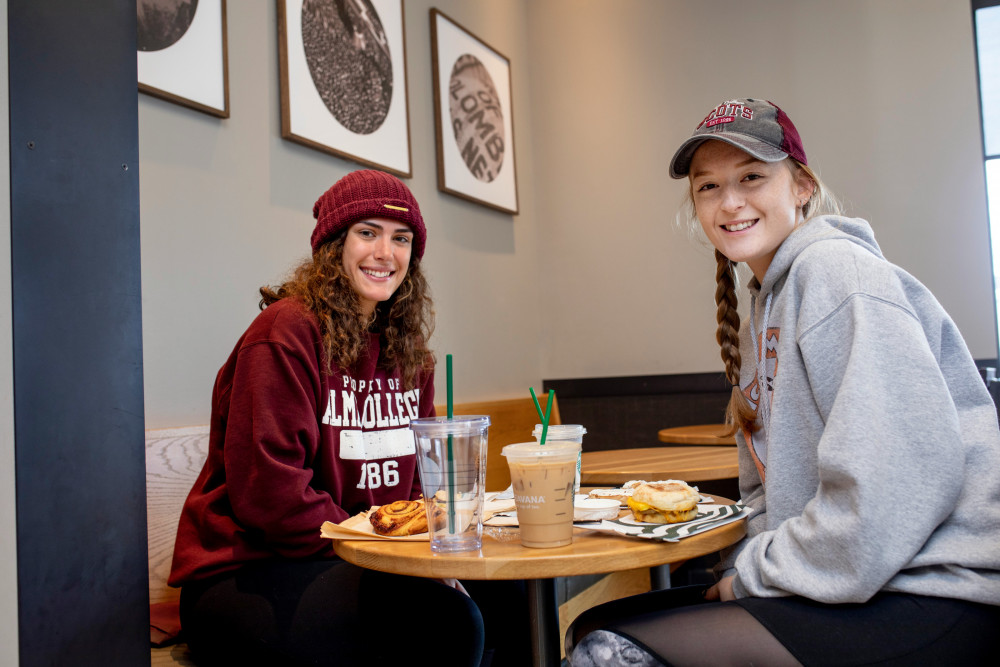 Two female students enjoy breakfast at a table inside the Alma College bookstore/Starbucks franchise.