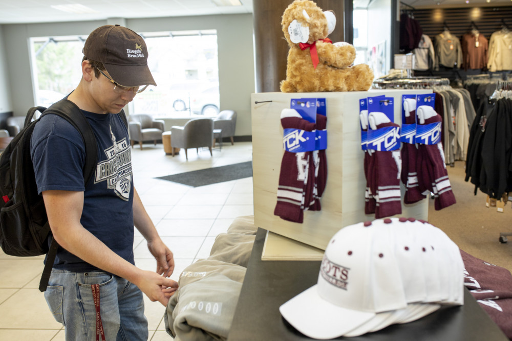 A male Alma College student in a blue tshirt, blue jeans, and a baseball cap peruses a stack of Alma College sweatshirts in the Alma College bookstore.