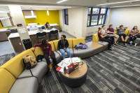 Students sit on a gray couch in a common area in the Newberry dormitory on the campus of Alma College