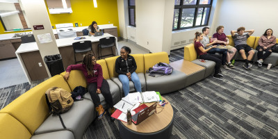 Students relax on a couch in a common area in an updated dormitory at Alma College