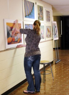 Student Annalise DeYoung hanging her artwork in the gallery for the senior show.