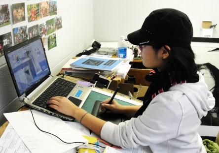Erin Chon working with a digital drawing tablet in her studio space.