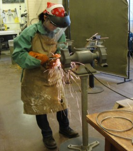 Student Erin Chon grinding metal in the tools and materials course.