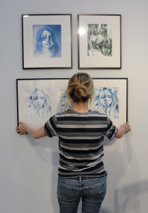 Student Amy Merriman hangs her work in the senior show, where each art major is given the opportu...