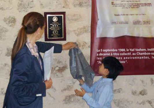 Edgar Flaud, the grandson of Annick Flaud, and his mother, Madame Flaud, unveil the plaque.