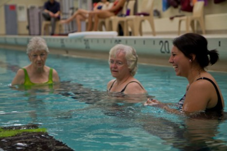 Students working with senior citizens in the pool studying the physiological effects of water aerobics.