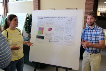 ASPIRE students Krystle Reiss and Chris McDonald present a poster about the Higgs boson.