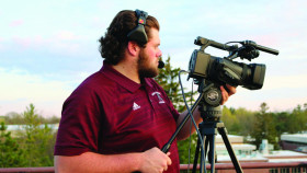 Student manning a camera during a live sports production.