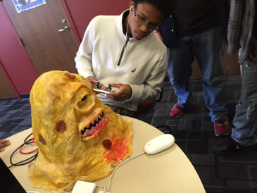 A visitor to campus takes a radioactive pizza monster by Nick Wracan (NMS '15) for a test drive.