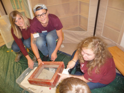 Robin Rooyakker ('19),  Anthropology major Maxim Short ('18),  and Natalie Sloggett ('17) lead children in exploring archaeology at Michigan Archaeology Day.