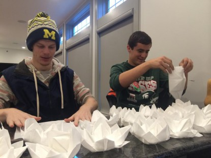 Noah and Luke are busy with folding napkins after Rieke's model